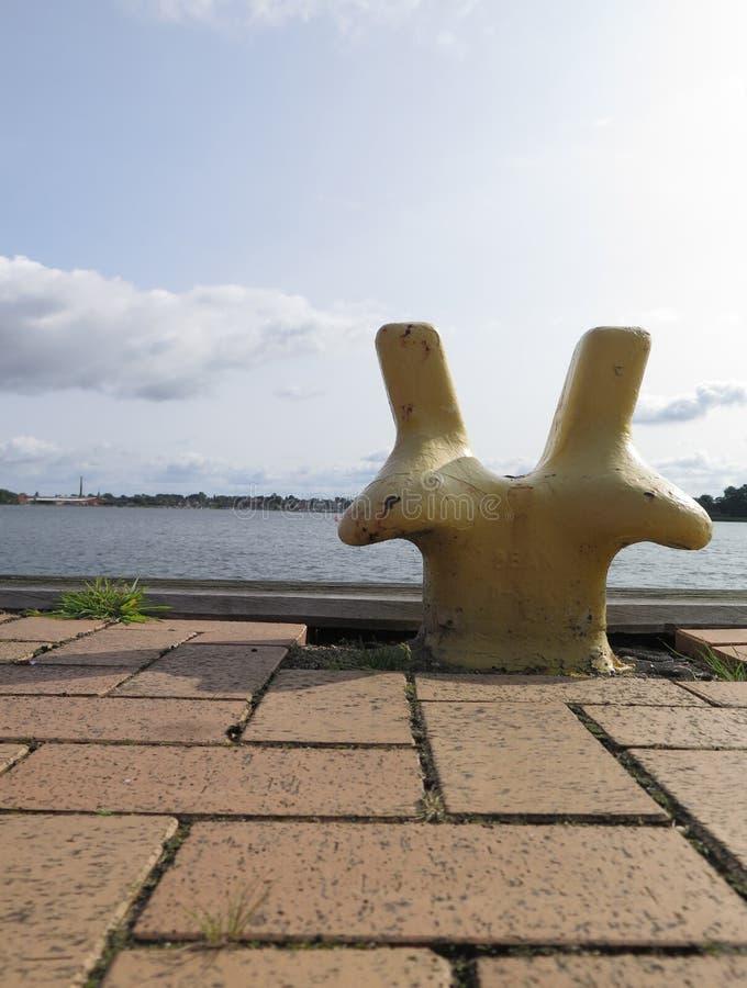 Poste de amarração amarelo no cais do porto fotografia de stock