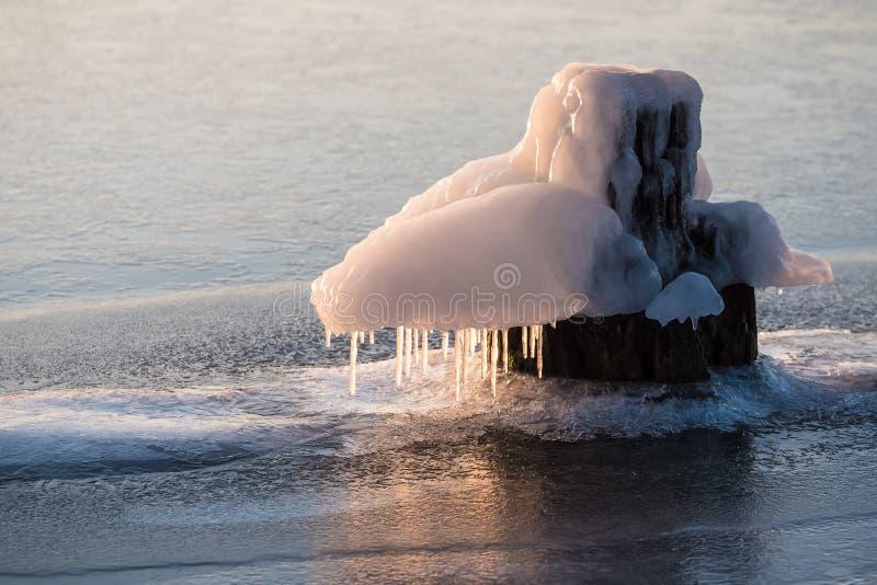 Poste de amarração congelado em um rio no inverno fotos de stock