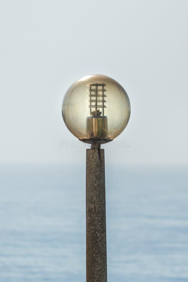 Poste de la lámpara cerca de una playa, con el océano como el fondo lagos imágenes de archivo libres de regalías