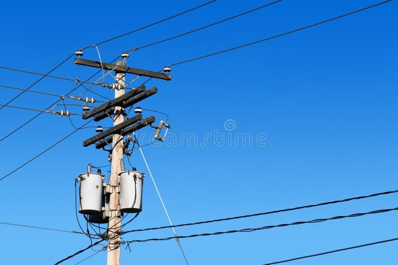 Poste de la línea eléctrica y cielo azul imagenes de archivo