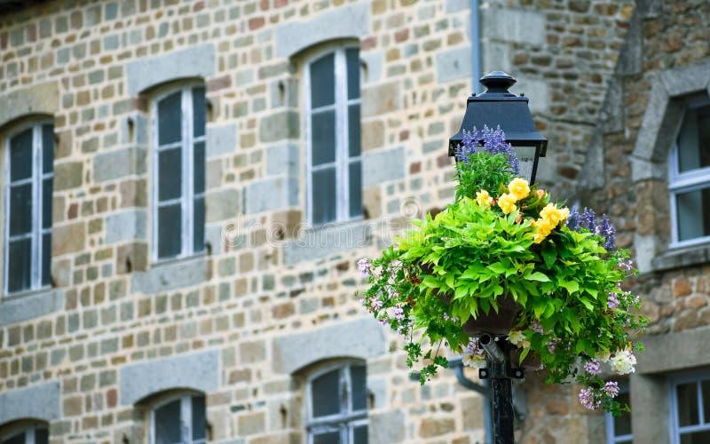 Poste de luz decorado com flores, com fundo defocused da casa típica do brittany francês imagens de stock royalty free