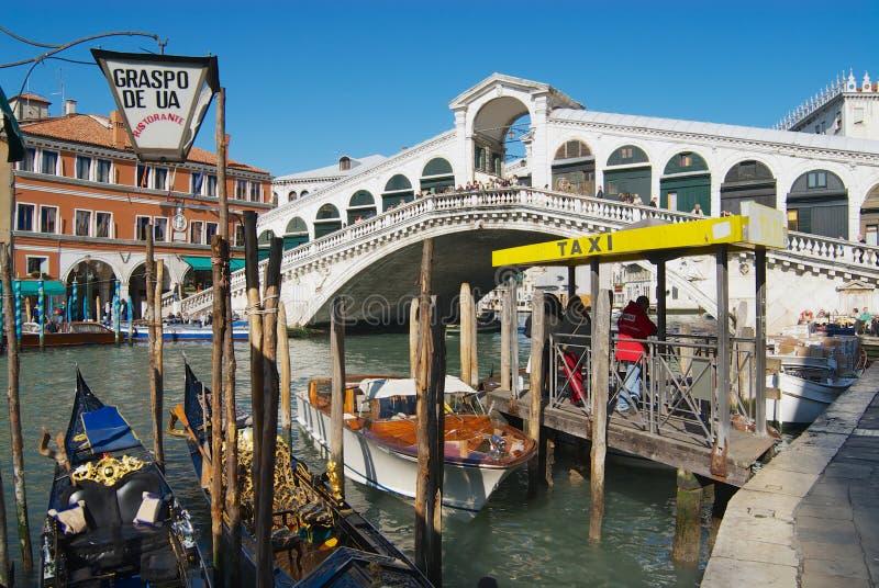 Poste del taxi al lado del puente de Ponte di Rialto de la señal sobre Grand Canal en Venecia, Italia imagen de archivo