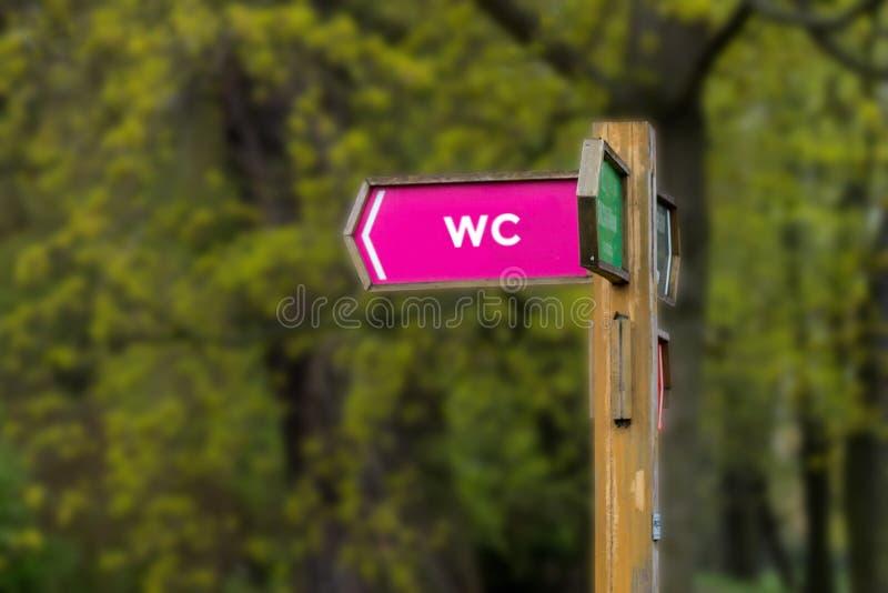 Poste indicador de madera delante de ?rboles verdes fotos de archivo libres de regalías