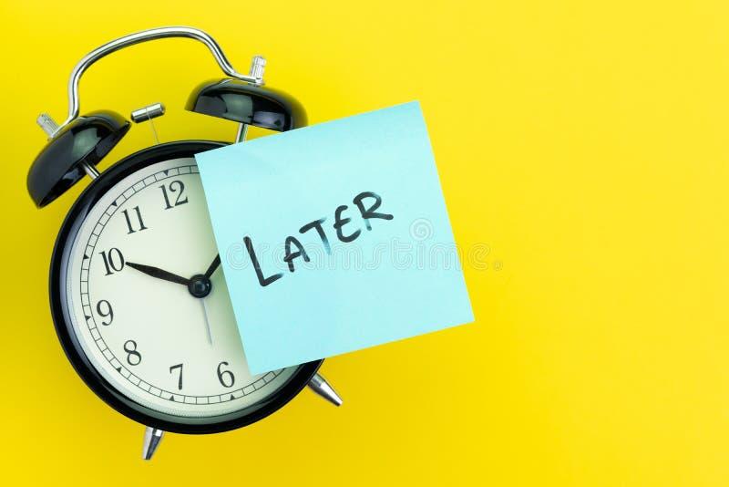 Poste pegajoso con escritura el palillo posterior de la palabra en el despertador en fondo amarillo sólido con el espacio de la c imagenes de archivo
