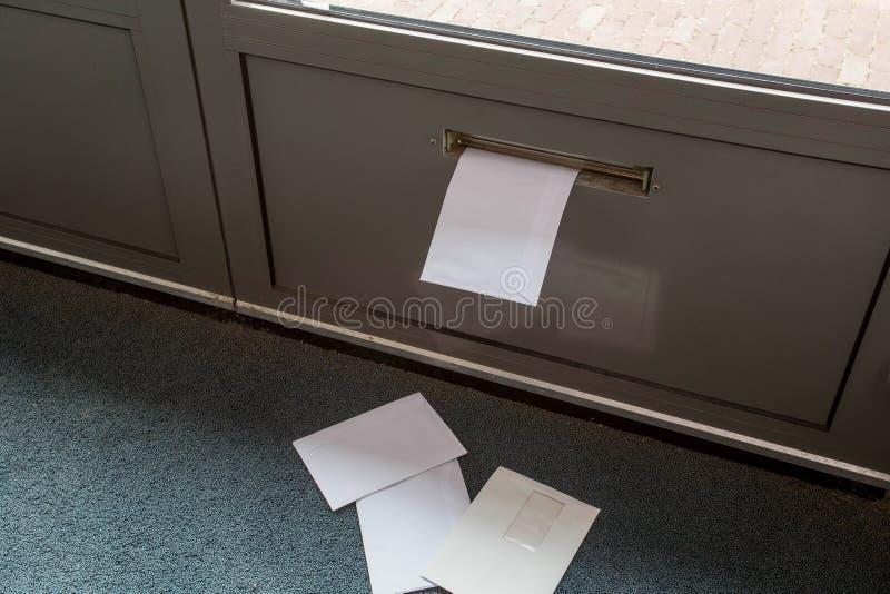 Poste que miente en el piso y en el buzón de la puerta en un edificio vacío imagen de archivo