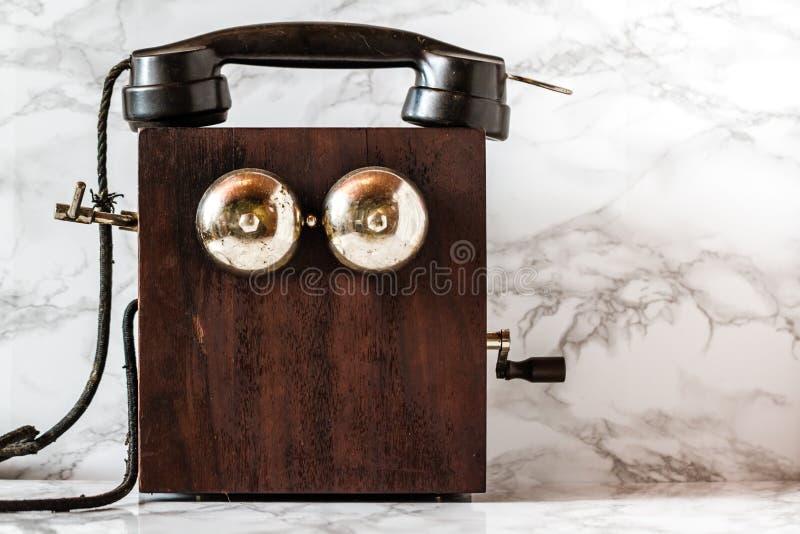 Poste téléphonique antique de manivelle de magnéto sur le fond de marbre photos stock
