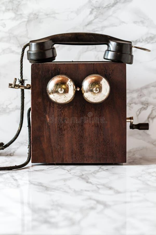 Poste téléphonique antique de manivelle de magnéto sur le fond de marbre photographie stock