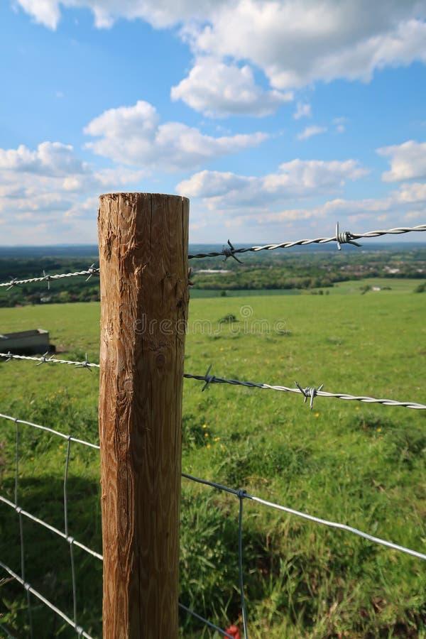 Posten- und Stacheldrahtzaun entlang Weideland auf dem Sussex Southdowns in England stockfotografie