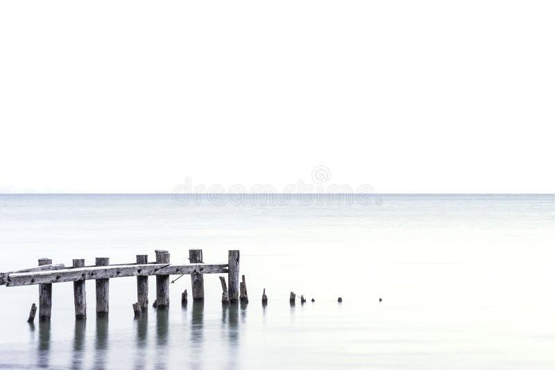 Posten van gebroken pijler die zich in een lichtblauw meer, witte hemelbedelaars bevinden royalty-vrije stock afbeeldingen