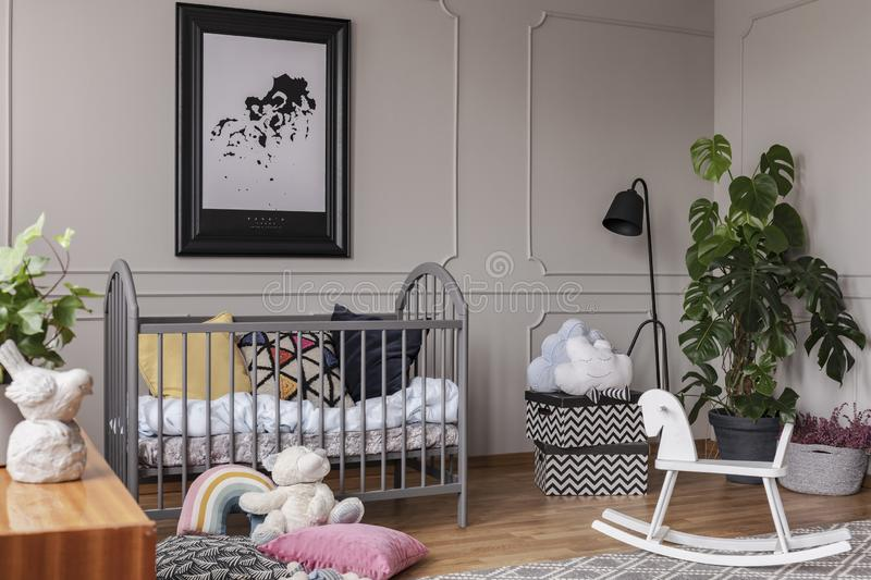 Poster above cradle next to toys in grey kid`s bedroom interior with plant and rocking horse. Real photo stock images