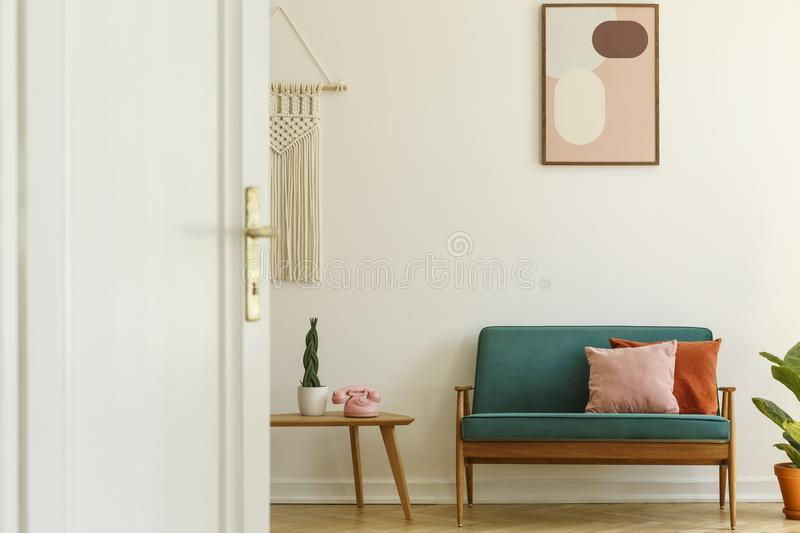 Poster above green couch with pillows in living room interior wi. Th plant on table. Real photo stock photo