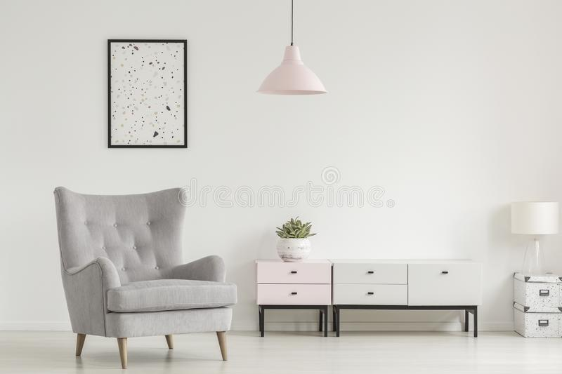 Poster above grey armchair and lamp in white living room interior with plant on cabinet. Real photo royalty free stock photos