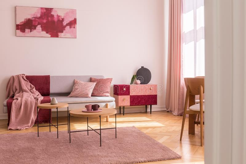 Poster above grey sofa with pillows in bright living room interior with table on pink carpet. Real photo. Concept photo stock image