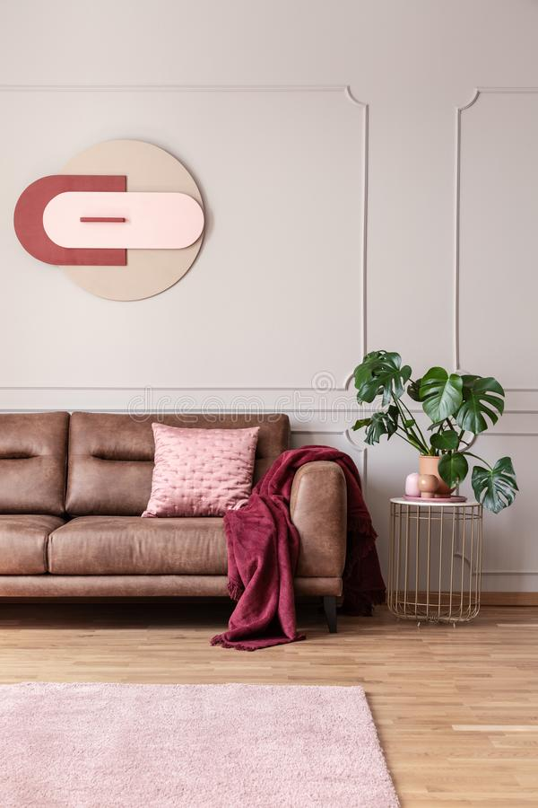 Poster above leather sofa in bright living room interior with carpet and plant on table. Real photo. Concept royalty free stock image