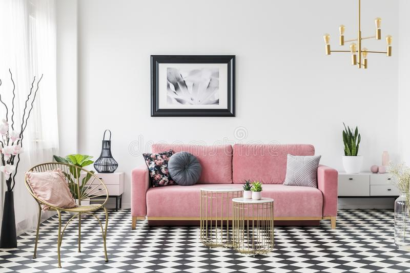 Poster above pink sofa in living room interior with gold armchair on checkered floor. Real photo stock photos