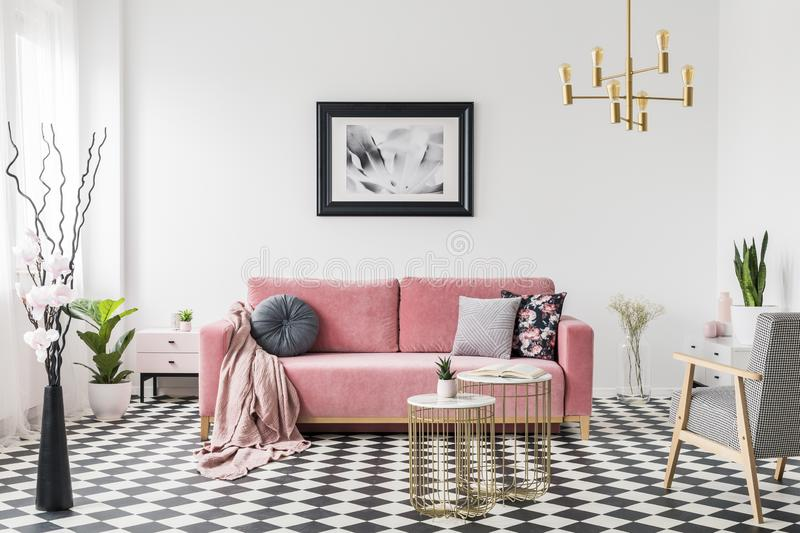 Poster above pink sofa in spacious living room interior with patterned armchair and plants. Real photo stock photos