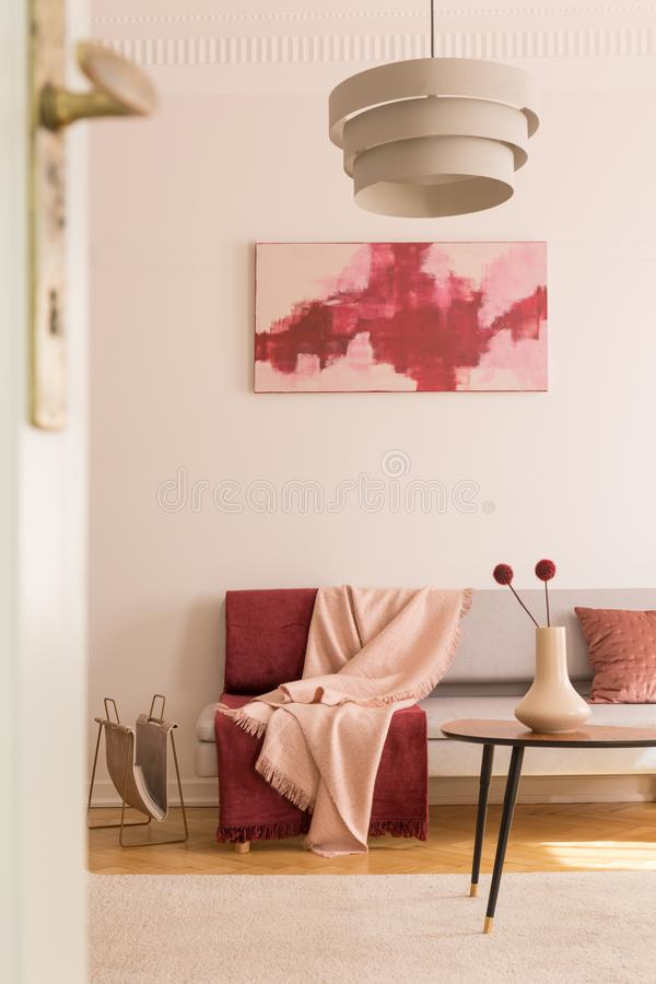 Poster above settee with blankets in loft interior with lamp above table with flowers. Real photo. Settee with blankets in loft interior with lamp above table stock images