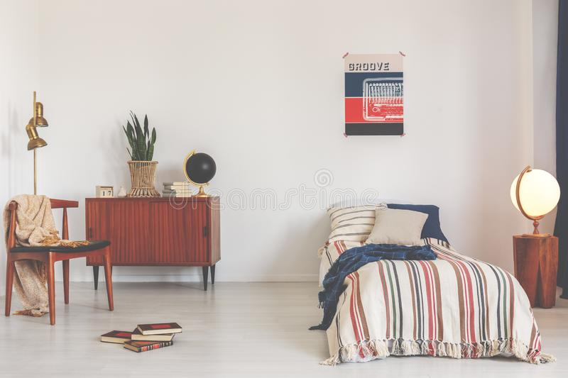 Poster above striped bed in white vintage bedroom interior with chair next to wooden cabinet. Real photo stock photo