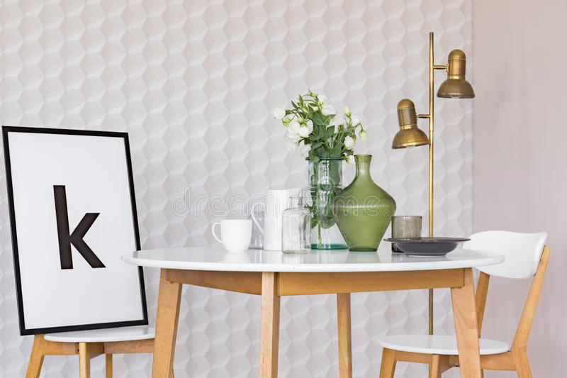 Poster in black frame on chair at wooden table with flowers in glass vase in classy dining room interior with geometric pattern on. Wallpaper stock photography