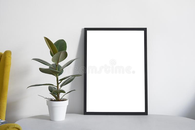 Poster A2 in black frame in nordic stylish modern interior, yellow armchair, ficus, living room. Empty space for design layout royalty free stock images