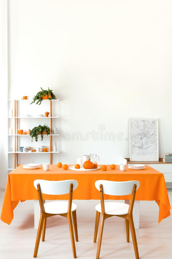 Poster on cabinet in white and orange dining room interior with wooden chairs at table. Real photo royalty free stock photography