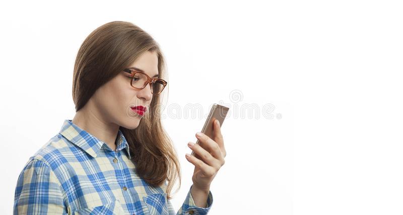 Shocked young woman in blue plaid shirt holding smartphone in hands. Poster design - Shocked young woman in blue plaid shirt holding smartphone in hands stock photo