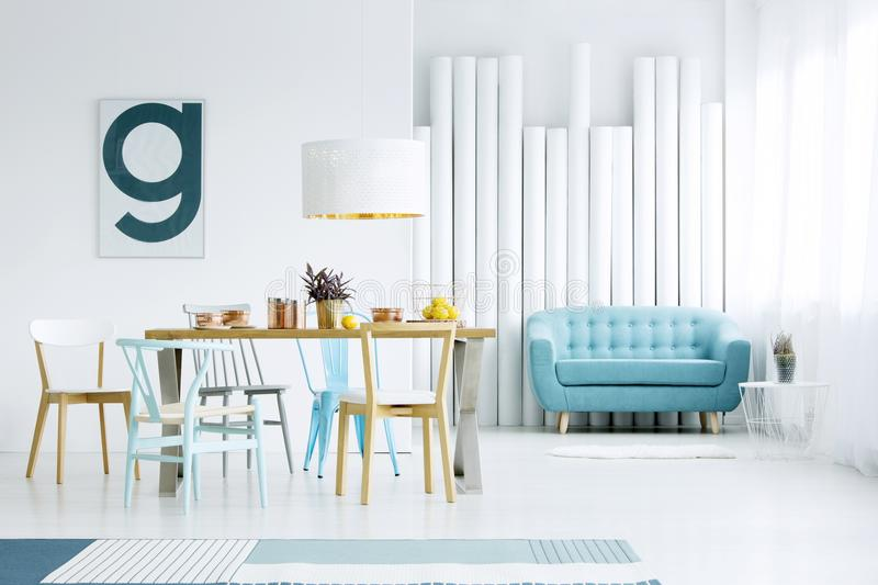 Poster in dining room interior. Simple poster hanging on white wall in dining room interior with wooden table, blue sofa and decorative tubes royalty free stock photo