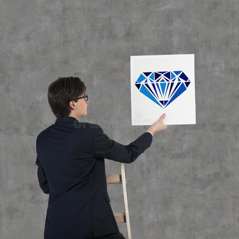 Poster with drawing brilliant. Businessman holding poster with drawing blue brilliant royalty free stock photos