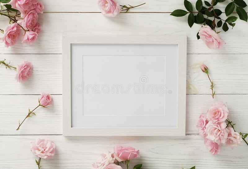Poster frame mockup, top view, pink roses on white wooden background.Holiday concept.Flat lay. Copy space royalty free stock images