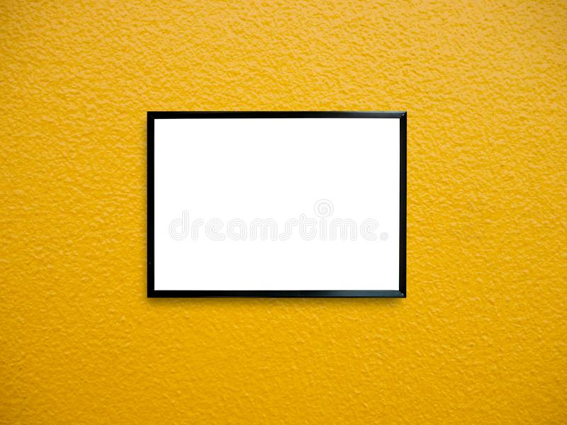 Poster frame on wall. Poster frame on yellow paint wall background royalty free stock photos