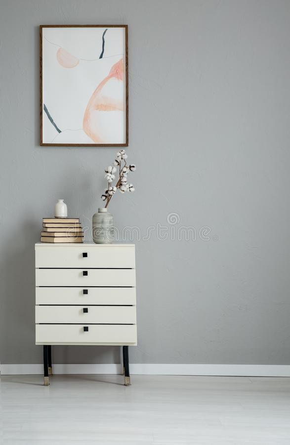Poster on grey wall above white cabinet with books and flowers in simple flat interior. Real photo royalty free stock photo