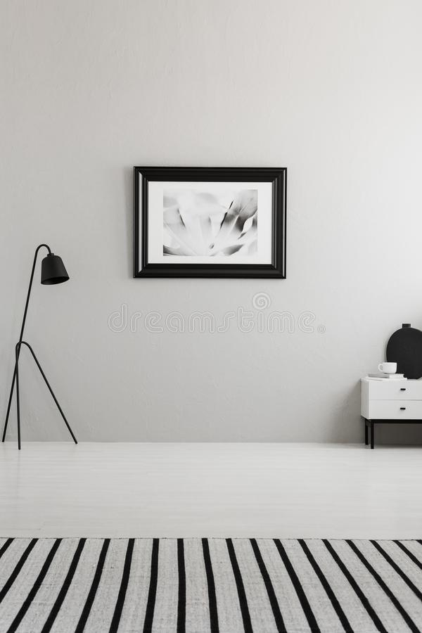 Poster on grey wall in living room interior with striped carpet. And black lamp. Real photo. Place for your sofa royalty free stock photos