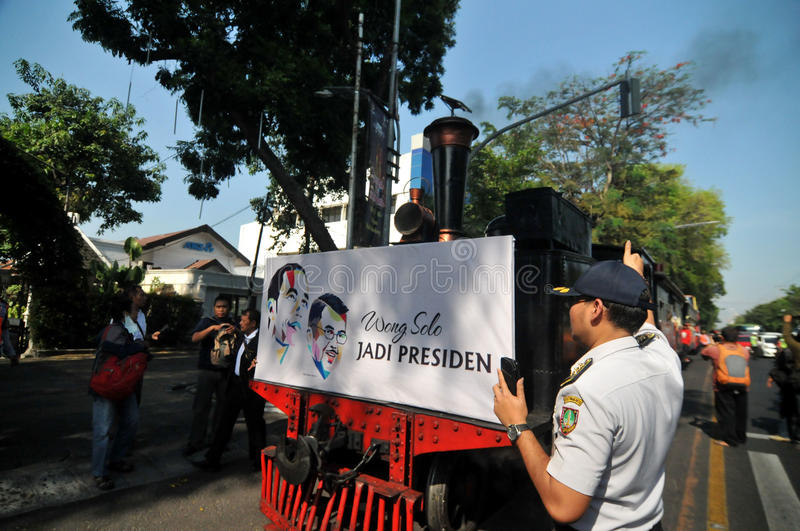 A poster of Joko Widodo-Kalla in front of a steam train. SURAKARTA, INDONESIA - October 20 : A poster of Indonesian new president Joko Widodo and his running royalty free stock photo