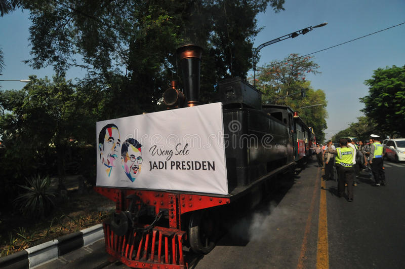 A poster of Joko Widodo-Kalla in front of a steam train. SURAKARTA, INDONESIA - October 20 : A poster of Indonesian new president Joko Widodo and his running royalty free stock images