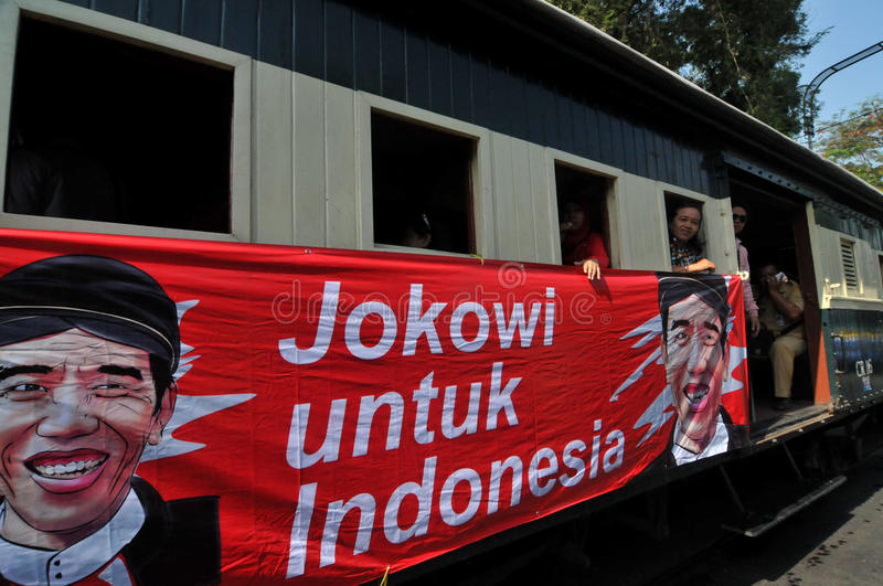 A poster of Joko Widodo-Kalla in front of a steam train. SURAKARTA, INDONESIA - October 20 : A poster of Indonesian new president Joko Widodo and his running royalty free stock photos