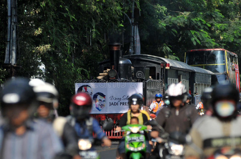 A poster of Joko Widodo-Kalla in front of a steam train. SURAKARTA, INDONESIA - October 20 : A poster of Indonesian new president Joko Widodo and his running stock image