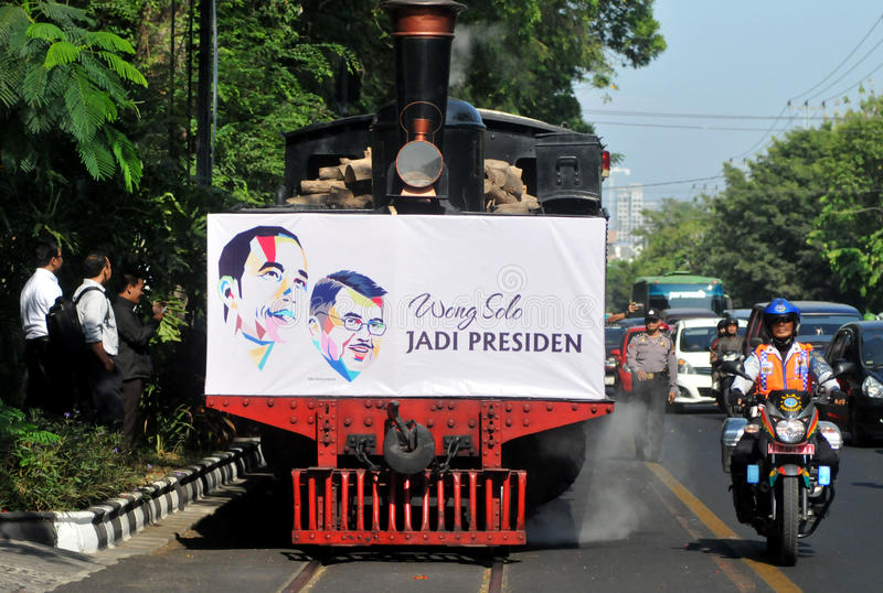 A poster of Joko Widodo-Kalla in front of a steam train. SURAKARTA, INDONESIA - October 20 : A poster of Indonesian new president Joko Widodo and his running stock photos