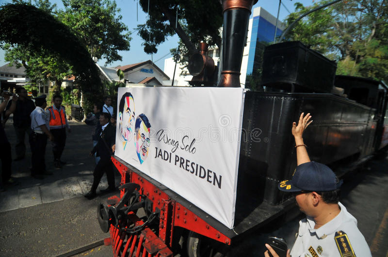 A poster of Joko Widodo-Kalla in front of a steam train. SURAKARTA, INDONESIA - October 20 : A poster of Indonesian new president Joko Widodo and his running stock photo
