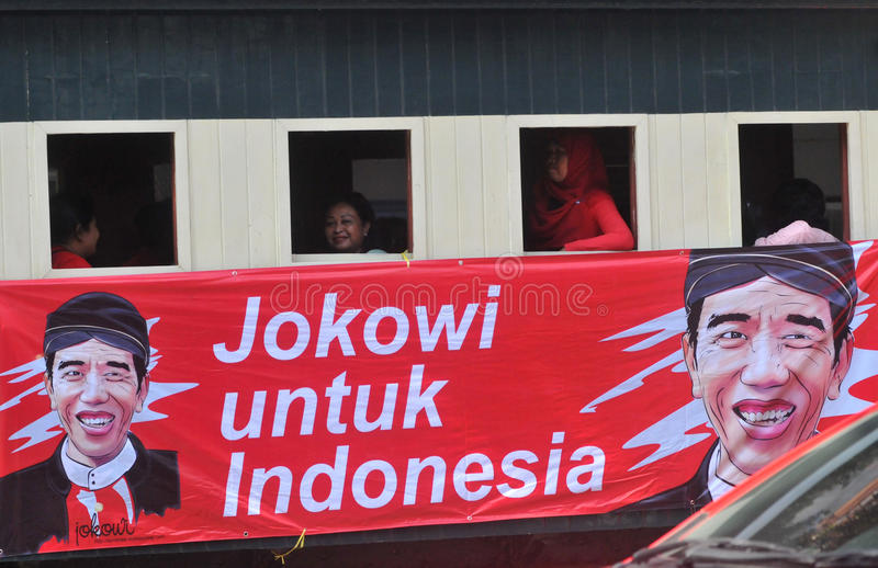 A poster of Joko Widodo-Kalla in front of a steam train. SURAKARTA, INDONESIA - October 20 : A poster of Indonesian new president Joko Widodo and his running stock images