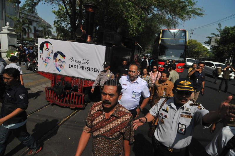A poster of Joko Widodo-Kalla in front of a steam train. SURAKARTA, INDONESIA - October 20 : A poster of Indonesian new president Joko Widodo and his running stock photography