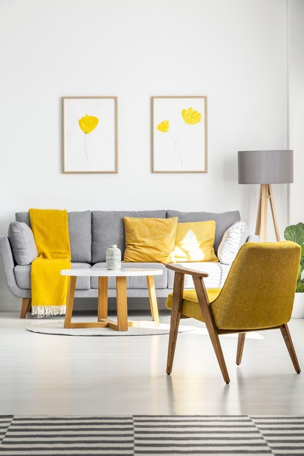 Poster mit den gelben Blumen, die über einer grauen Couch in hellem hängen stockfotos