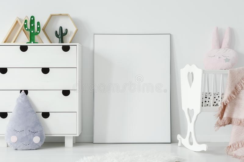 Poster with mockup between white cradle and cabinet in child`s r stock photography