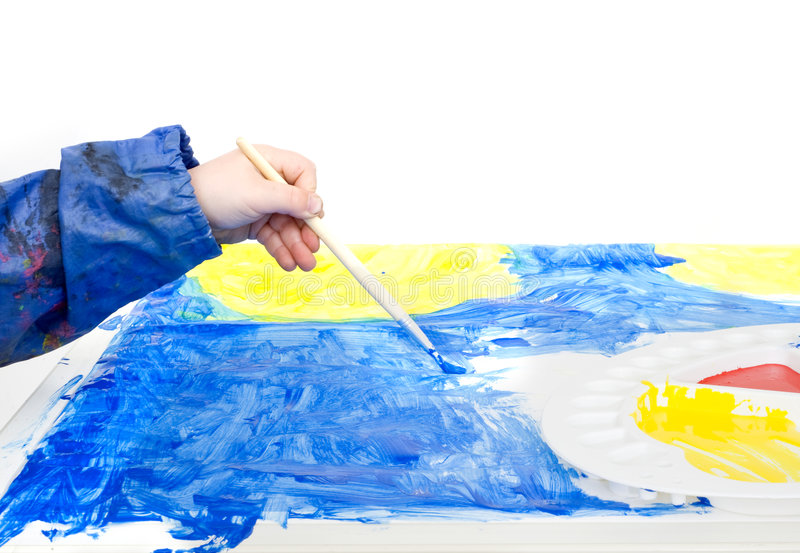 Poster painting. The hand of a young child holding a brush with blue poster paint royalty free stock image