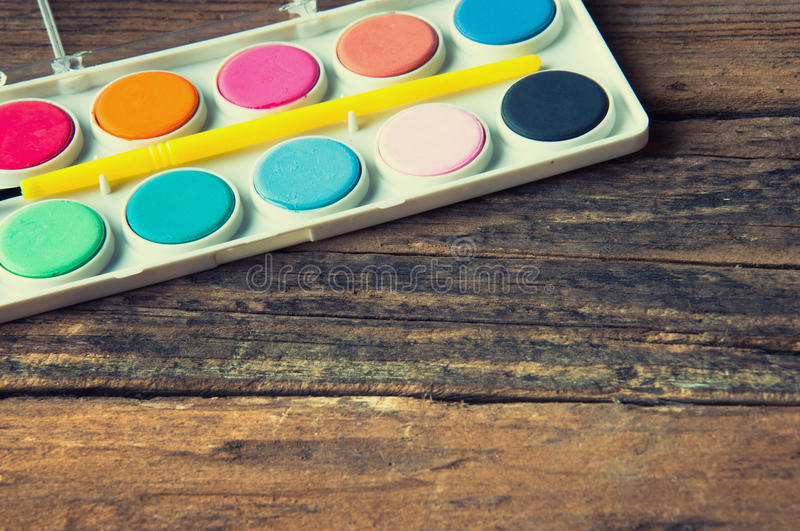 Poster paints and brush on vintage wooden table. Copyspace royalty free stock photo
