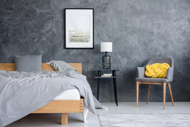 Poster on texture wall. Minimal poster hanging on grey texture wall in room with wooden bed and armchair with yellow knot pillow royalty free stock photography