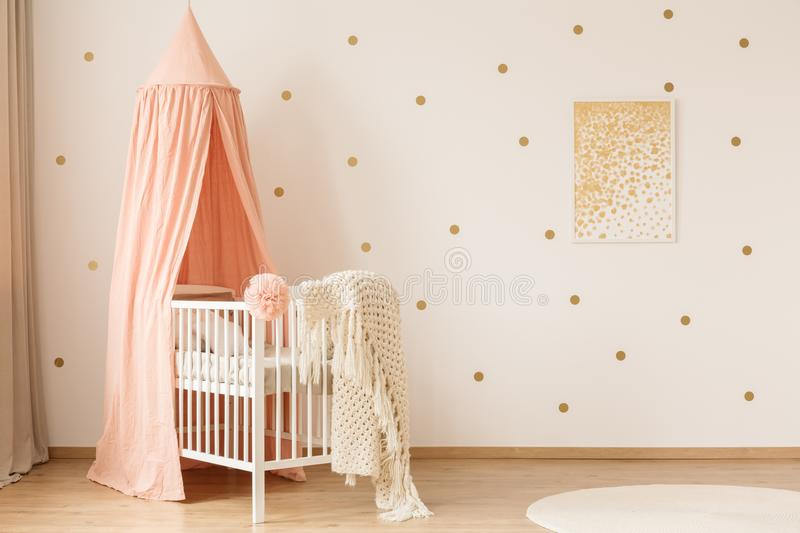 Poster on the wall. Simple gold poster hanging on white wall in baby room interior with dirty pink canopy and crib royalty free stock photos