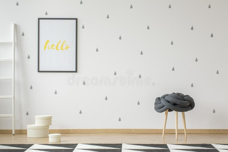 Poster on wallpaper in teenager`s room interior with stool and g. Eometric carpet. Real photo with a place for your desk stock photography