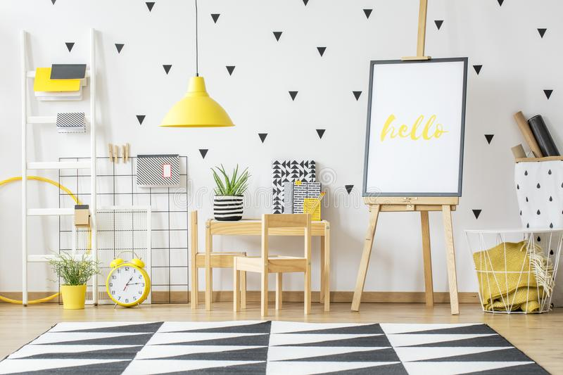 Poster on a wooden easel and a small desk for children in a whit. E, scandi style preschool room interior with white wall and vibrant, yellow decorations stock image