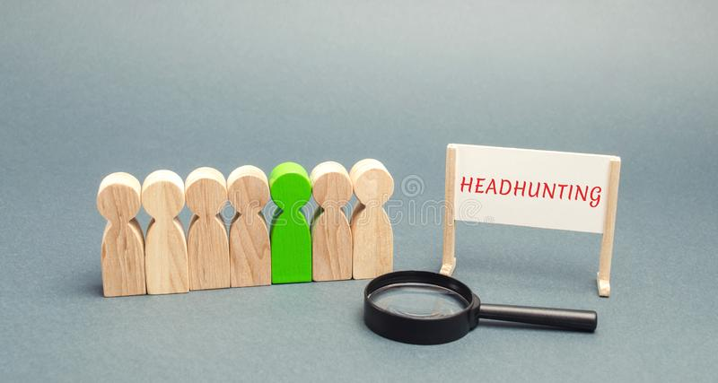 A poster with the word Headhunting, a crowd of people and a magnifying glass. The concept of hiring people to work. Staff. Recruitment. Search for employees stock photos