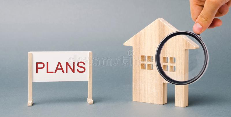 A poster with the word Plans and a miniature wooden house. Property investment. Estate planning. Living trust. Rental housing. Tax stock image